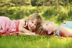 Mutter und ihre kleine Tochter liegen auf dem Gras lizenzfreie stockbilder