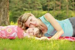 Mutter und ihre kleine Tochter liegen auf dem Gras stockbilder