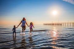 Mutter und ihre Söhne springen auf das Meer lizenzfreie stockfotos