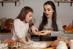 Mutter und ihre Tochter backen ein Brot und haben Spaß an der Küche stockfoto