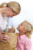 Mutter und ihre Tochter, die Lebensmittelgeschäftbeutel entpacken lizenzfreies stockfoto