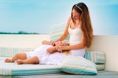 Mutter und ihre Tochter entspannen sich im Seehintergrund Stockfoto