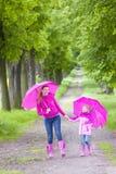 Mutter und ihre Tochter mit Regenschirmen Stockfotografie