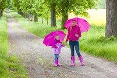 Mutter und ihre Tochter mit Regenschirmen Stockbild