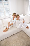 Mutter und jugendliche Tochter, die auf weißem Sofa sich entspannen Lizenzfreie Stockfotos