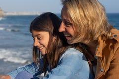 Mutter und jugendliche Tochter, die durch das Mittelmeer lachen lizenzfreie stockfotografie