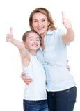 Mutter und junge Tochter mit den Daumen oben Stockbilder