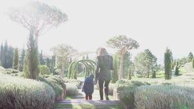 Mutter und junger Sohn gehen durch den Park stock footage