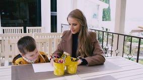 Mutter und junger Sohn zeichnen an einem Tisch stock video