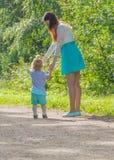 Mutter und Kind auf einem Weg im Park Lizenzfreie Stockbilder