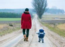 Mutter und Kind auf sandiger Straße lizenzfreie stockfotos