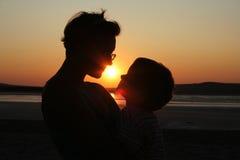 Mutter und Kind auf Sonnenuntergang Stockbild
