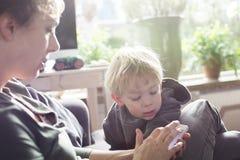 Mutter und Kind, das Smartphone verwendet Stockbilder