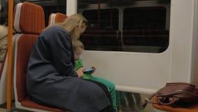 Mutter und Kind, das Zelle in beweglicher Untergrundbahn verwendet stock video footage
