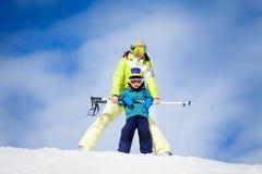 Mutter und Kind in den Masken, die mit Ski stehen, stimmt ab Lizenzfreies Stockbild