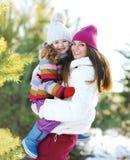 Mutter und Kind, die den Spaß draußen spielt im Winter hat Stockfoto