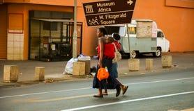 Mutter und Kind, die eine Straße in im Stadtzentrum gelegenem Johannesburg kreuzen Lizenzfreie Stockfotos