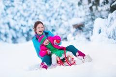 Mutter und Kind, die in einem schneebedeckten Park rodeln Stockfoto