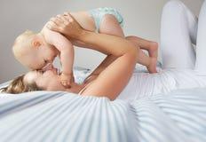 Mutter und Kind, die lachen und spielen Stockbild
