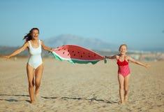 Mutter und Kind, die lustiges Wassermelonentuch und -c$laufen halten lizenzfreies stockfoto