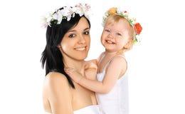 Mutter und Kind, die mit Blume lächeln Stockfotografie