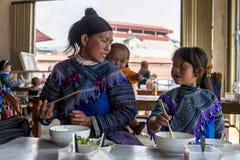 Mutter und Kind, die Mittagessenmahlzeit im shophouse bei Sapa Vietnam haben Stockbilder