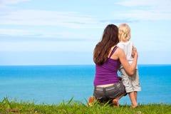Mutter und Kind, die schöne Ozeanansicht betrachten Stockbilder