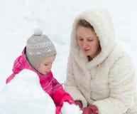 Mutter und Kind, die Schneemann machen lizenzfreie stockbilder