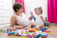 Mutter und Kind, die zu Hause Blockspielwaren spielen Stockfotos