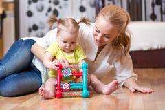 Mutter und Kind, die zu Hause Blockspielwaren spielen Stockbild