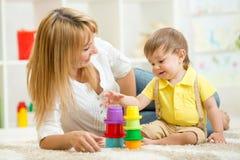 Mutter und Kind, die zu Hause Blockspielwaren spielen Stockfoto