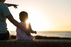 Mutter und Kind, die zusammen auf dem Strand, den schönen Sonnenuntergang aufpassend sitzt Stockfoto