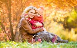Mutter und Kind, die zusammen im Herbstpark sitzen und umarmen Stockfotografie