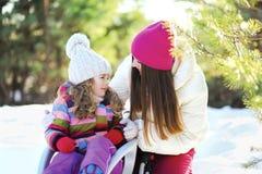 Mutter und Kind im Schlitten, der Spaß, sonnigen Winter hat Stockbilder
