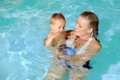 Mutter und Kind im Swimmingpool stockbilder