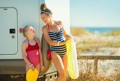 Mutter und Kind mit dem gelben aufblasbaren Rettungsring, der jedes betrachtet stockfotos
