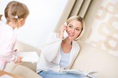 Mutter und Kind - am Telefon im Wohnzimmer Lizenzfreies Stockbild