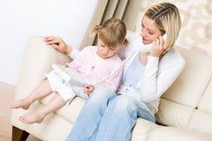 Mutter und Kind - am Telefon im Wohnzimmer Stockfoto