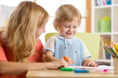 Mutter und Kind von drei Jahren den Spaß habend, der zu Hause malt Stockfotografie