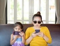 Mutter und Kindaddictation Handy stockfoto