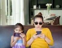 Mutter und Kindaddictation Handy lizenzfreie stockfotografie