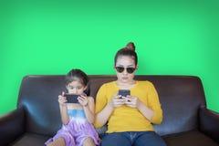 Mutter und Kindaddictation Handyspiel auf grünem Schirm stockfoto