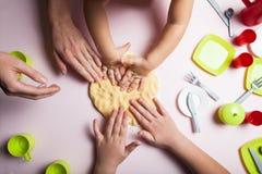 Mutter und Kinder backen Plätzchen in der Küche und verzieren Plätzchen auf Weihnachtsabend, die Draufsicht stockfotografie