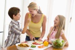 Mutter und Kinder bereiten a-Mahlzeit vor Lizenzfreie Stockfotos