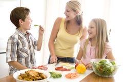 Mutter und Kinder bereiten a-Mahlzeit vor Stockfotos