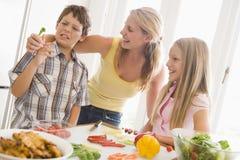Mutter und Kinder bereiten a-Mahlzeit vor Lizenzfreie Stockfotografie