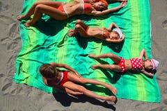 Mutter und Kinder, die auf Bettdecke auf Strand liegen Lizenzfreies Stockfoto