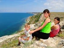 Mutter und Kinder, die auf dem Rand sitzen Stockfotos