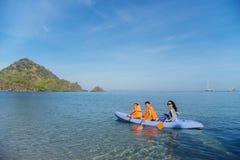 Mutter und Kinder, die auf dem Strand Kayak fahren Stockfotografie