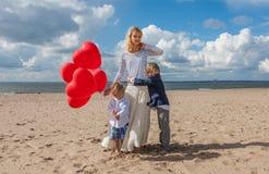 Mutter und Kinder, die auf dem Strand umarmen Lizenzfreies Stockbild
